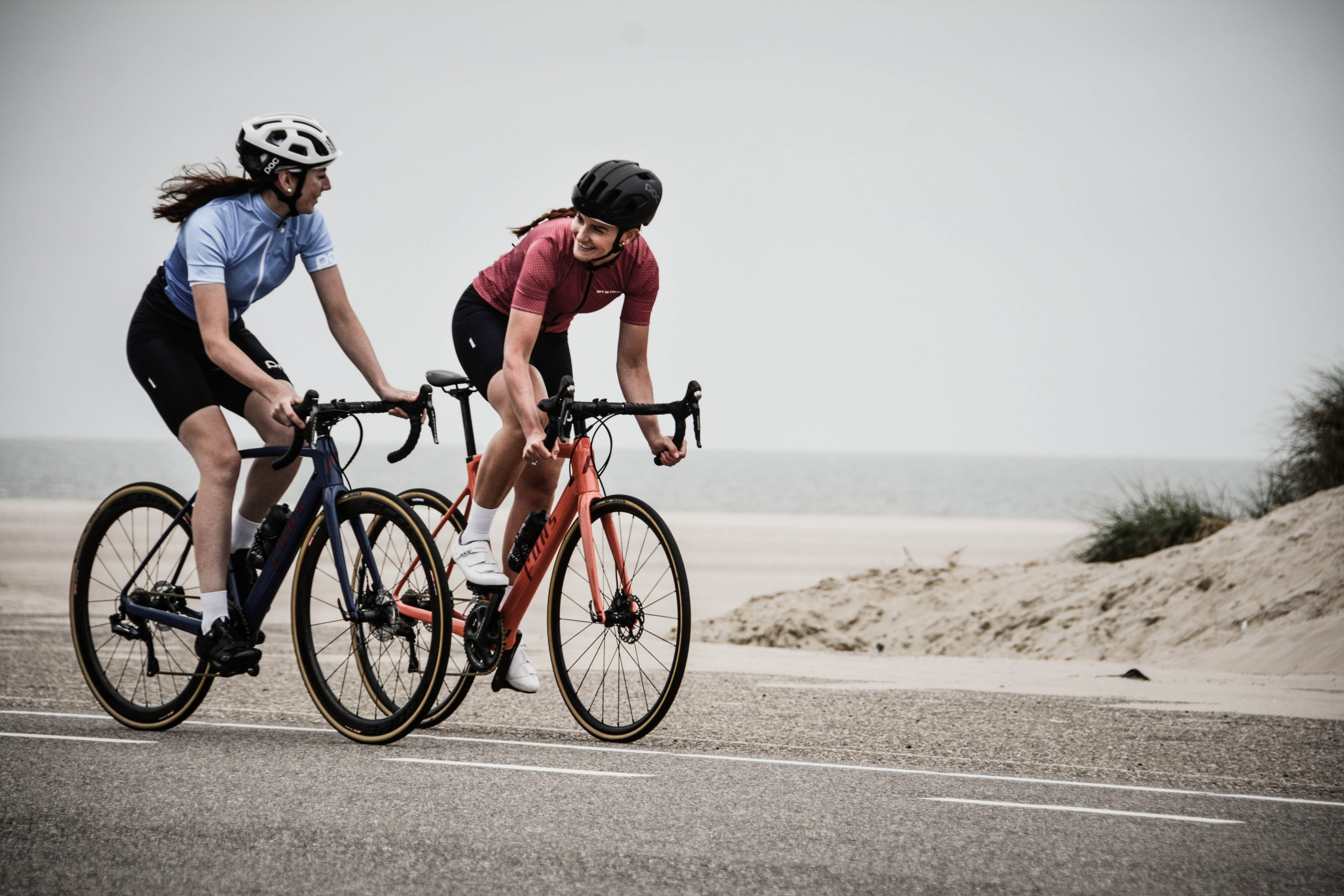 man and woman riding road bikes at the road near shore